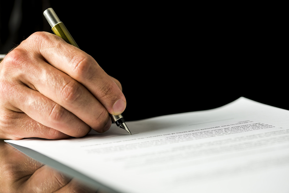 man signing document with a pen